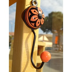 orange round ceramic coat hook with black flower